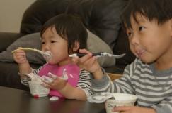 Boy and girl eating yogurt together