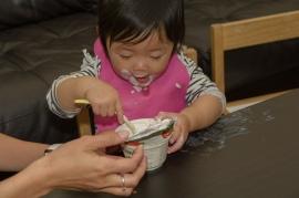 Infant feeding herself yogurt