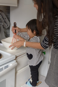 Little girl on stool in kitchen