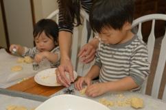 Mom helping a boy press a cookie cutter