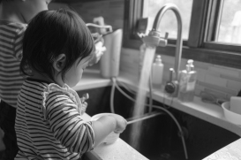 Girl playing in kitchen sink