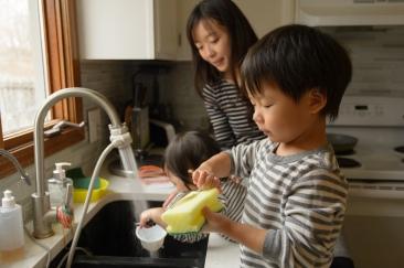Little boy washing dishes