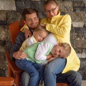 Family of four sitting on one chair