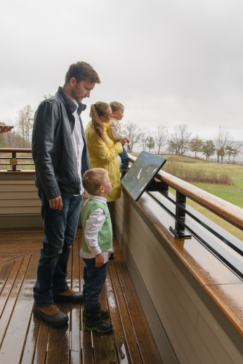 Family on balcony looking at informational sign
