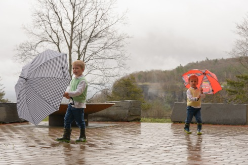 Two boys playing with umbrellas