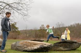 Boy jumping between rocks