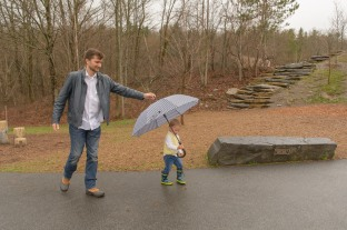 Dad holding onto son's umbrella