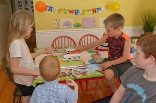 Kids looking at birthday cake together