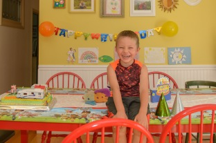 Smiling boy sitting on table next to cake