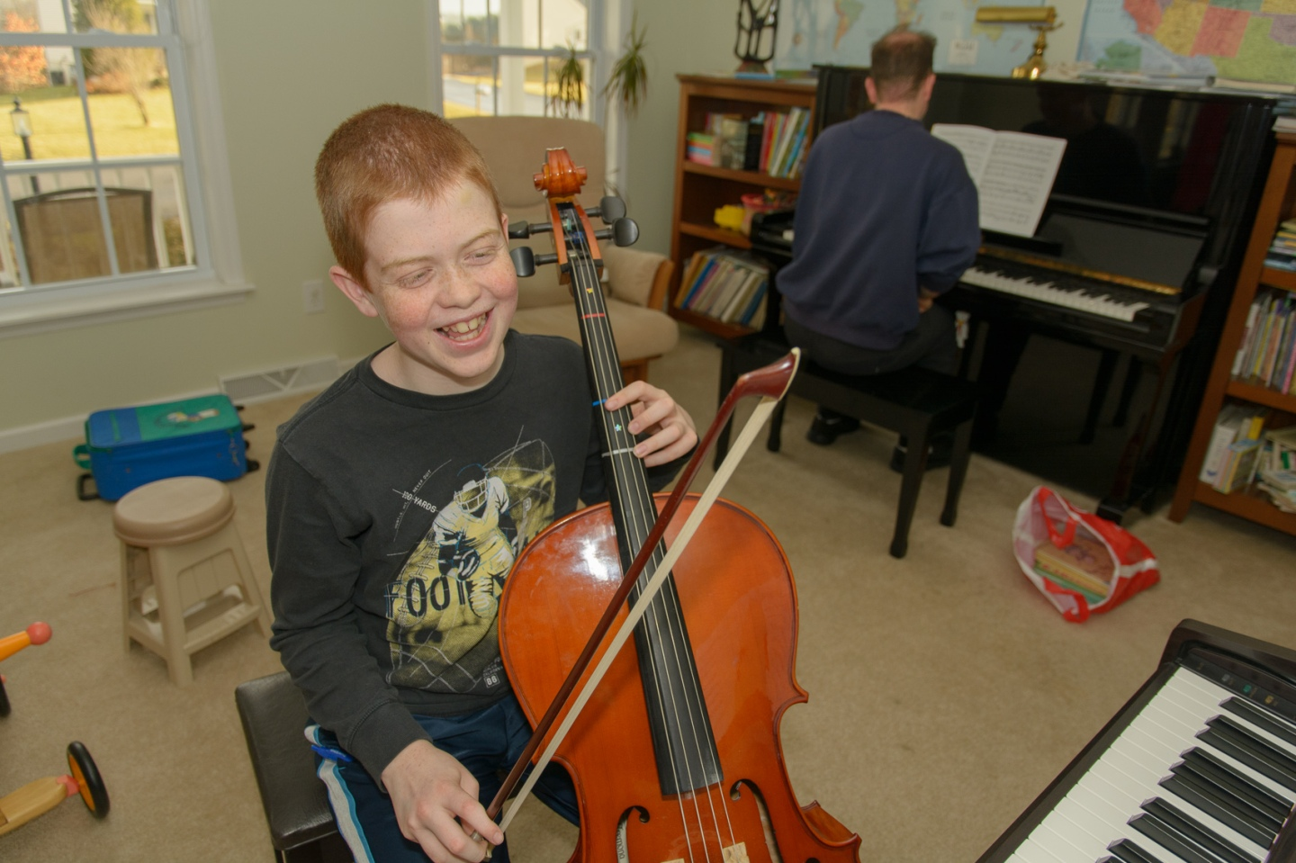 boy laughing while playing cello