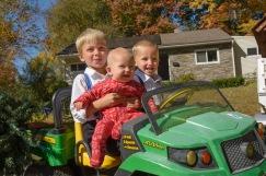 Three kids smiling on John Deere Ride