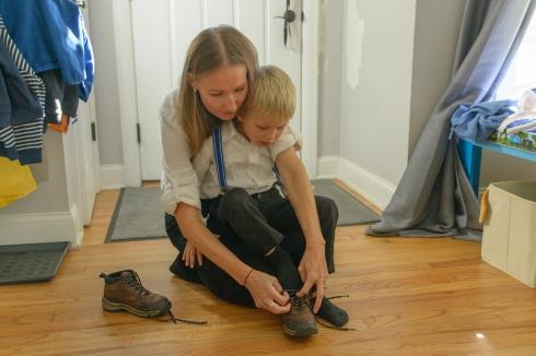 Mom helping boy tie shoe