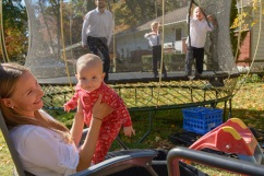 Family jumping on trampoline with mom and baby