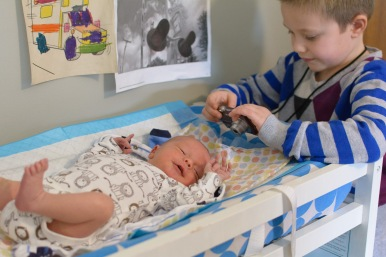 Big brother taking picture of newborn brother