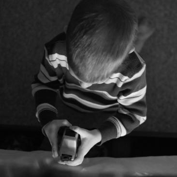 preschooler kneeling by bed