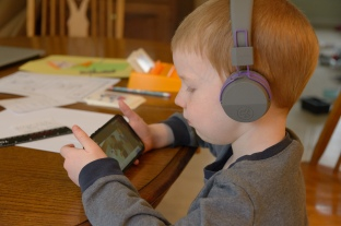 child with headphone watching video