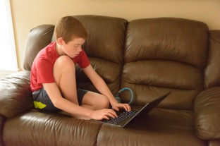 boy working on laptop on couch