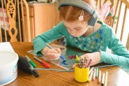 girl drawing Easter eggs on foil