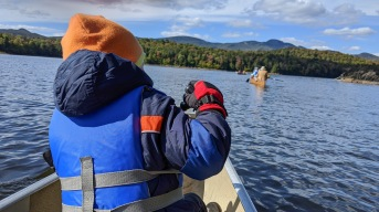 boy in warm clothes paddling canoe