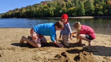 siblings burying brother in sand