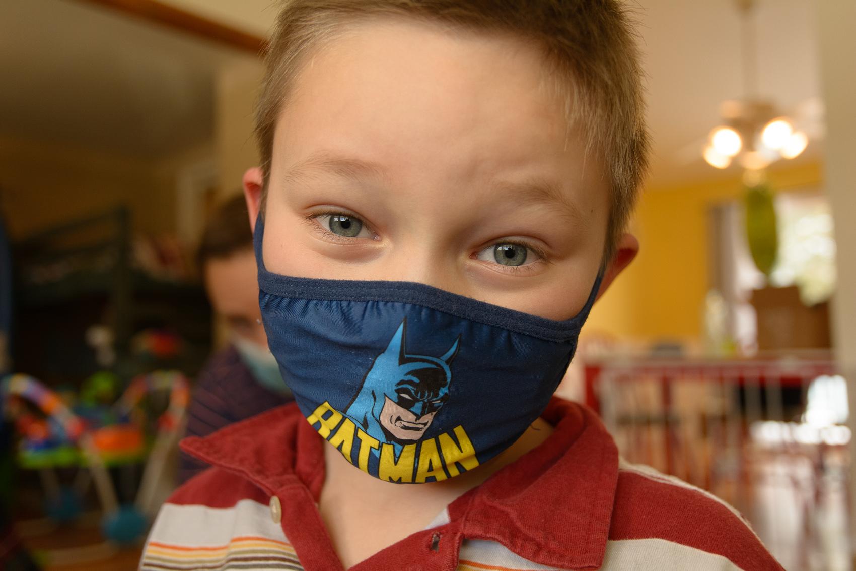boy smiling behind mask