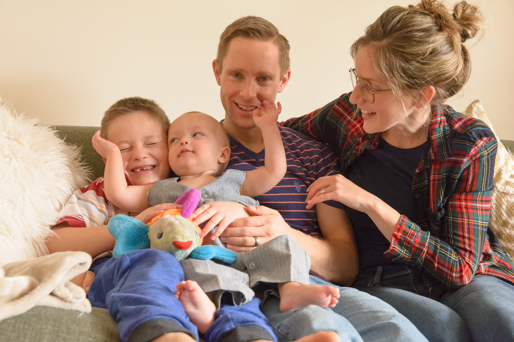 infant hugging brother and family on couch