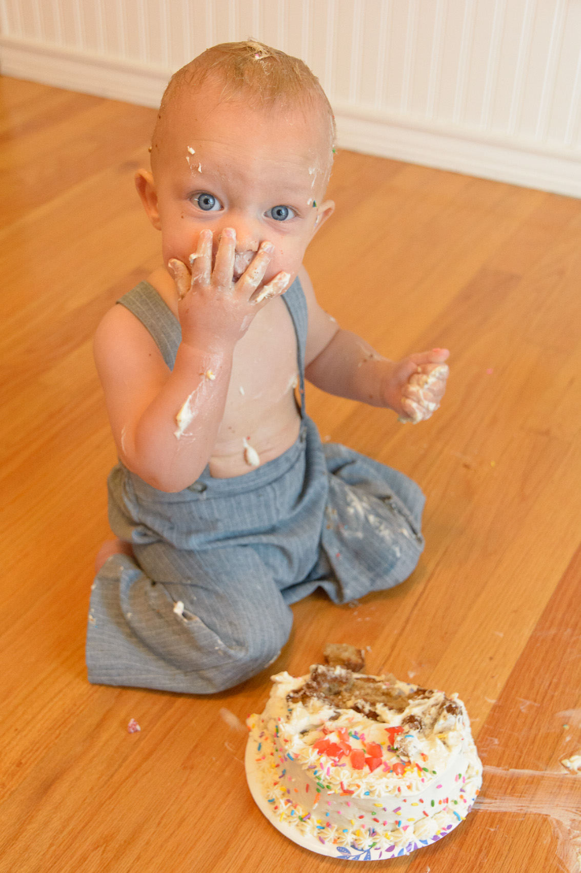 baby licking frosting off his palm