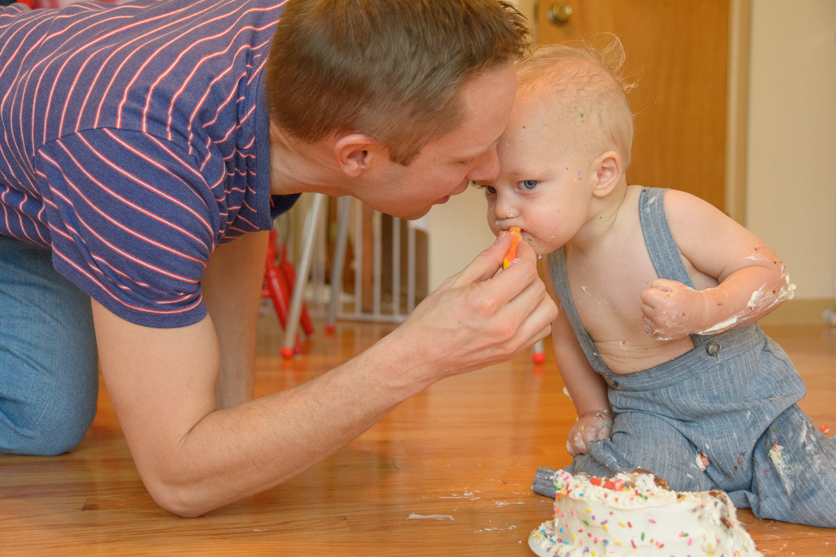 dad and baby sharing frosting off a cake